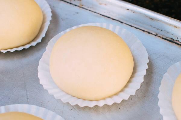 3. Подготовьте небольшие бумажные (можно по рецепту приготовления красивых булочек из дрожжевого теста использовать также формы для кексов) формочки. Разделите тесто на 12-15 одинаковых кусочков. Скатайте шарики и выложите в формочки. Дайте тесту еще раз подойти, для этого оставьте его примерно на 1 час.