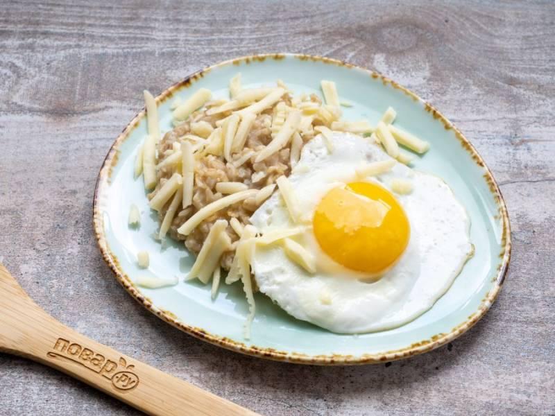 На тарелку выложите порцию каши, яйцо. Посыпьте сыром и зеленью. Готово!