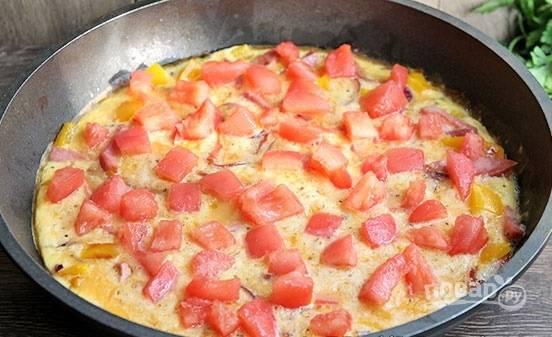"""Заливаем яичной смесью и готовим на слабом огне. Как только омлет """"схватится"""", распределяем по его поверхности кусочки помидоров. Накрываем крышкой и готовим омлет на слабом огне в течение 3-5 минут."""