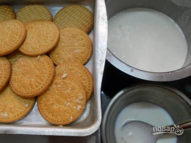 Молоко влейте в миску, каждую печеньку обмакните в молоко и выложите на дно глубокой формы.