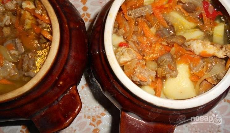 Сверху выкладываем грибы с мясом и овощами. Доливаем воду, чтобы та покрыла содержимое. Также добавляем соль и перец по вкусу. Немного перемешиваем и отправляем горшочки в духовку на 1 час, температура 200 градусов.