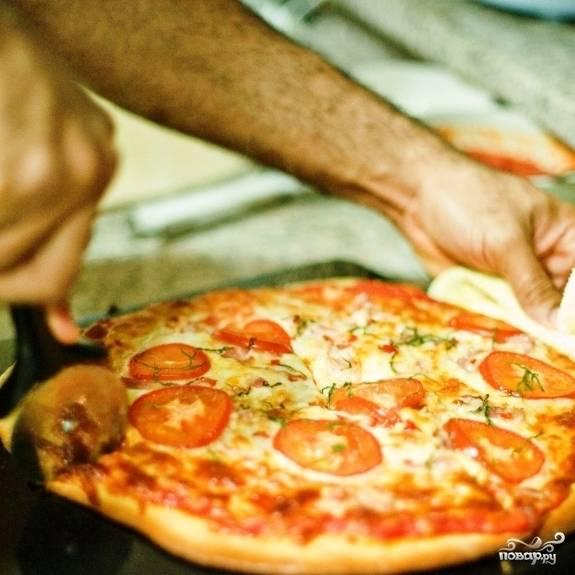 Ставим в разогретую до 230 градусов духовку и запекаем около 20 минут. Готовую пиццу достаем из духовки, сбрызгиваем оливковым маслом, нарезаем и немедленно подаем.