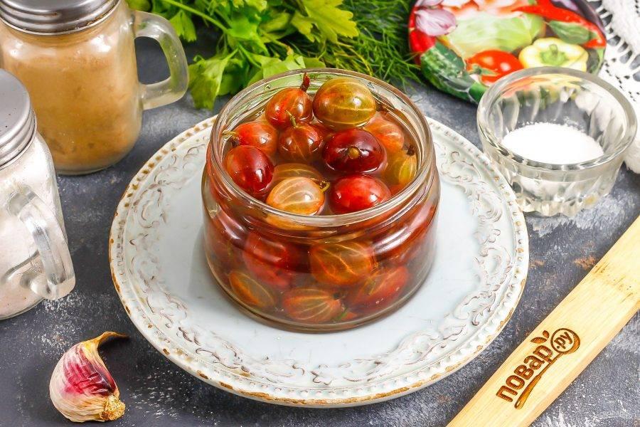 Из емкости с ягодами слейте воду в кастрюлю. Вскипятите жидкость в кастрюле и влейте уксус, выключите нагрев.