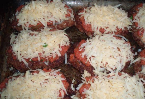 Формируем из фарша большие и тонкие котлетки, слегка обжариваем их на сковороде и кладем на противень. Для соуса: измельчаем в блендере помидоры и чеснок, добавляем туда же томатный соус и специи. Получается густой томатный соус. Кладем на шницели: порезанный колечками лук, поливаем томатным соусом, присыпаем тертым сыром. Запекаем в духовке до красивой румяной корочки, примерно 20-25 минут.