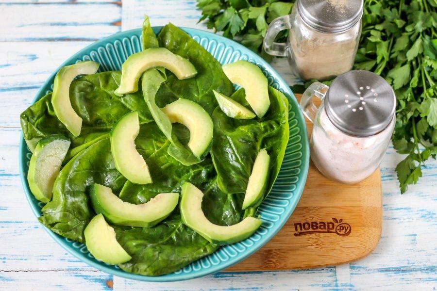 Авокадо очистите от кожуры, разрезав пополам и удалив косточку. Затем нарежьте каждую половинку слайсами и выложите на шпинат.