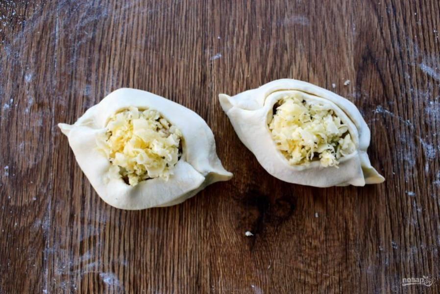 5.     В центр заготовки поместите начинку, сверху посыпьте тертым сыром. Сформируйте лодочки. Потяните полоски к центру, перекрестите над начинкой и расположите их внахлест на противоположные края.