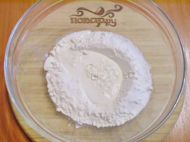 Муку смешиваем в глубоком посудине с содой. Вливаем кефир. Ложкой начинаем замешивать тесто. В процессе вливаем масло.