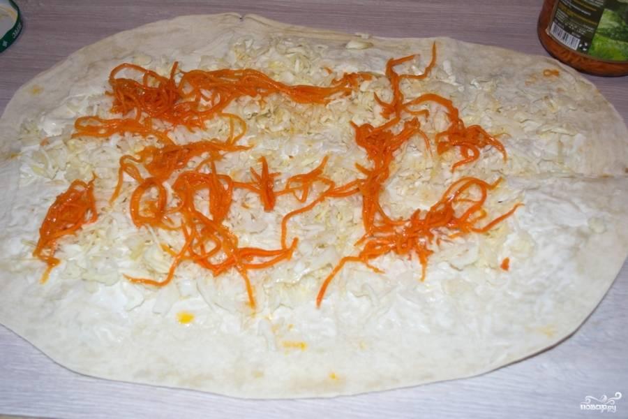 Морковь по-корейски отожмите от маринада и распределите сверху на капусте.