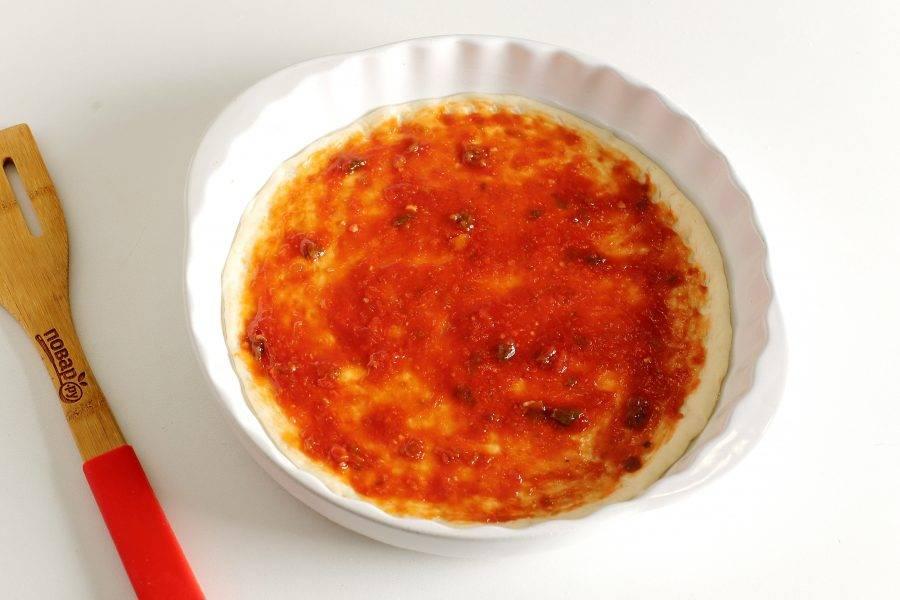 Смажьте тесто томатным соусом.
