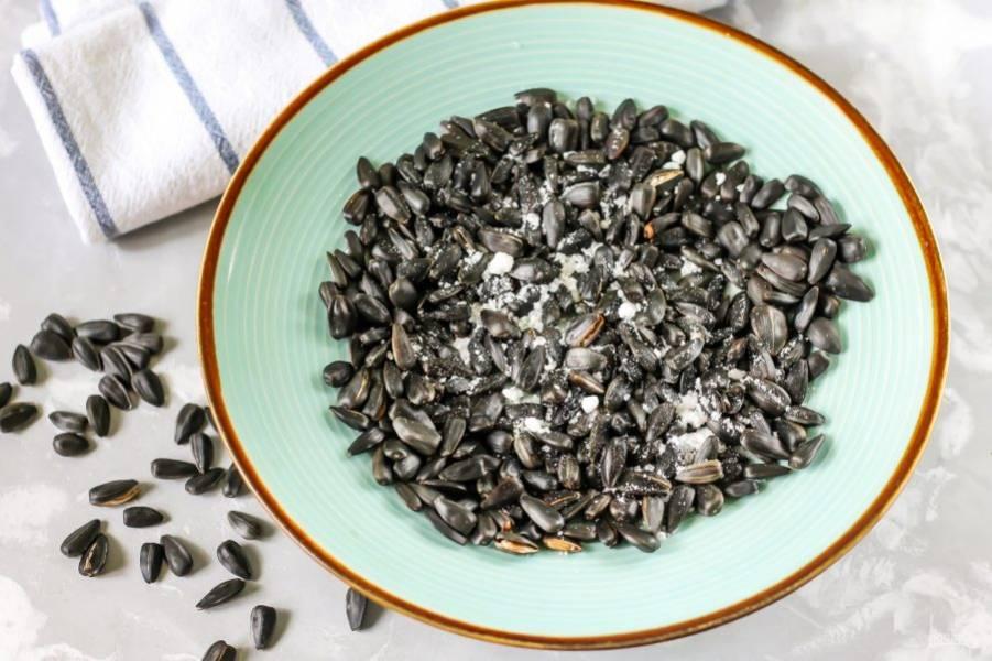Извлеките тарелку из микроволновки и всыпьте соль, перемешайте и оставьте семечки остывать на 7-8 минут.