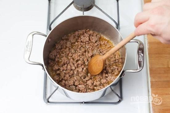 2.В кастрюле разогрейте 2 столовые ложки растительного масла, выложите фарш и обжарьте его, регулярно перемешивая, около 2-3 минут. Выложите к нему лук и чеснок, готовьте еще пару минут.
