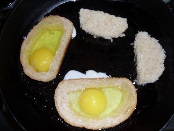 Ставим разогреваться сковороду с растительным маслом, а сами тем времени аккуратно вырезаем из ломтиков батона мякиш. В разогретое масло выкладываем батон и в каждый ломтик разбиваем по одному яйцу, солим его по вкусу. Накрываем сковороду крышкой и жарим бутерброды на маленьком огне, пока яичный белок не застынет, затем переворачиваем их и обжариваем с другой стороны до золотистой корочки.