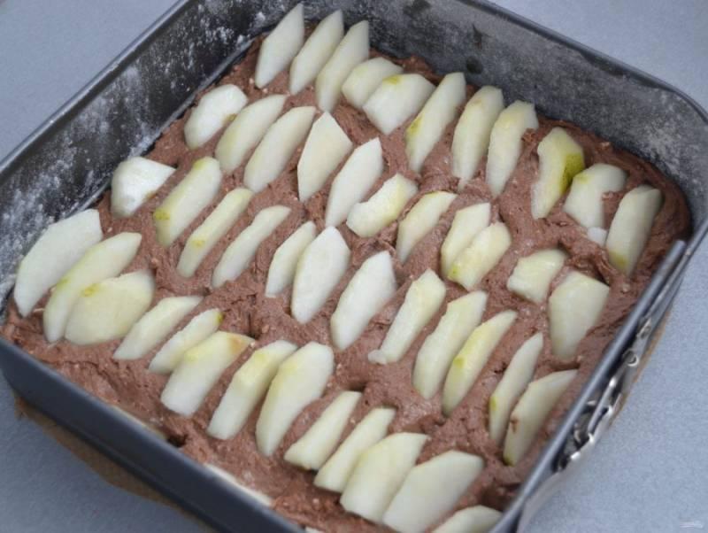 Выложите тесто в форму для выпечки, разровняйте. Очистите груши, нарежьте ломтиками, уложите вертикально, рядами в тесто.