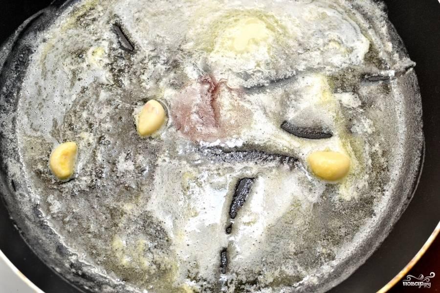 В небольшой ёмкости разведите крахмал в молоке. Пока отставьте мисочку. Растопите на сковороде с высокими бортиками сливочное масло. Добавьте зубчики чеснока, обжаривайте, пока чеснок не даст аромат и не размягчится. Постоянно помешивайте, иначе чеснок подгорит.