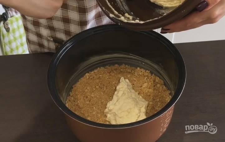 8. Дно и бока чаши мультиварки смажьте маслом. Утрамбуйте пальцами крошку из печенья, делая небольшие бортики. Затем выложите половину теста и разровняйте.