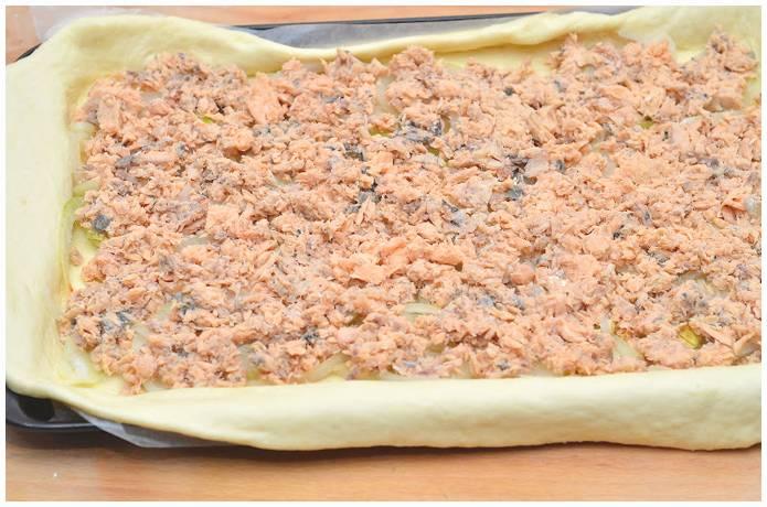 5. Раскатываем пласт теста и выкладываем его в форму для выпекания. Сверху выкладываем нашу начинку - консервы и лук.
