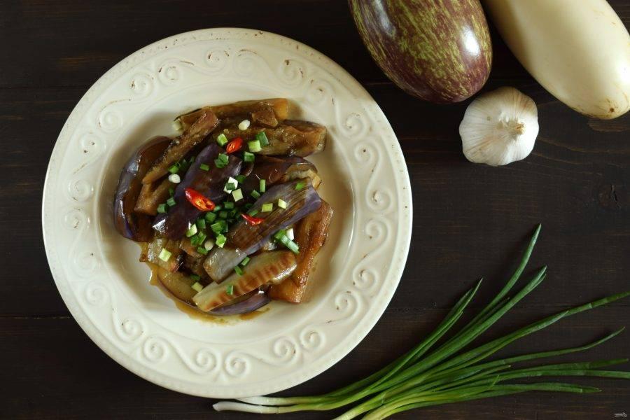 Разложите баклажаны по тарелкам, посыпьте мелко нарезанным чили и зеленым луком. Приятного аппетита!
