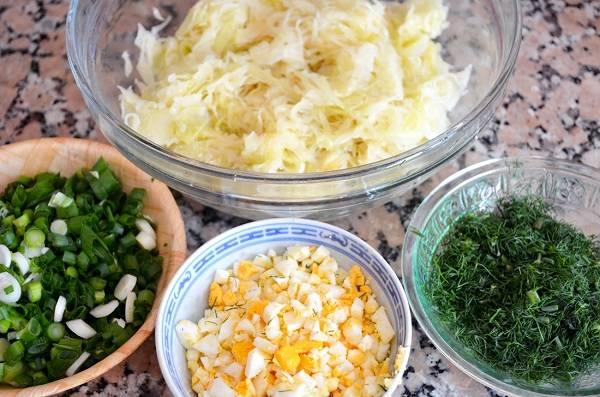 4. Остудите до комнатной температуры капусту, а тем временем вымойте и измельчите зелень по вкусу, нарежьте мелкими кубиками яйцо.