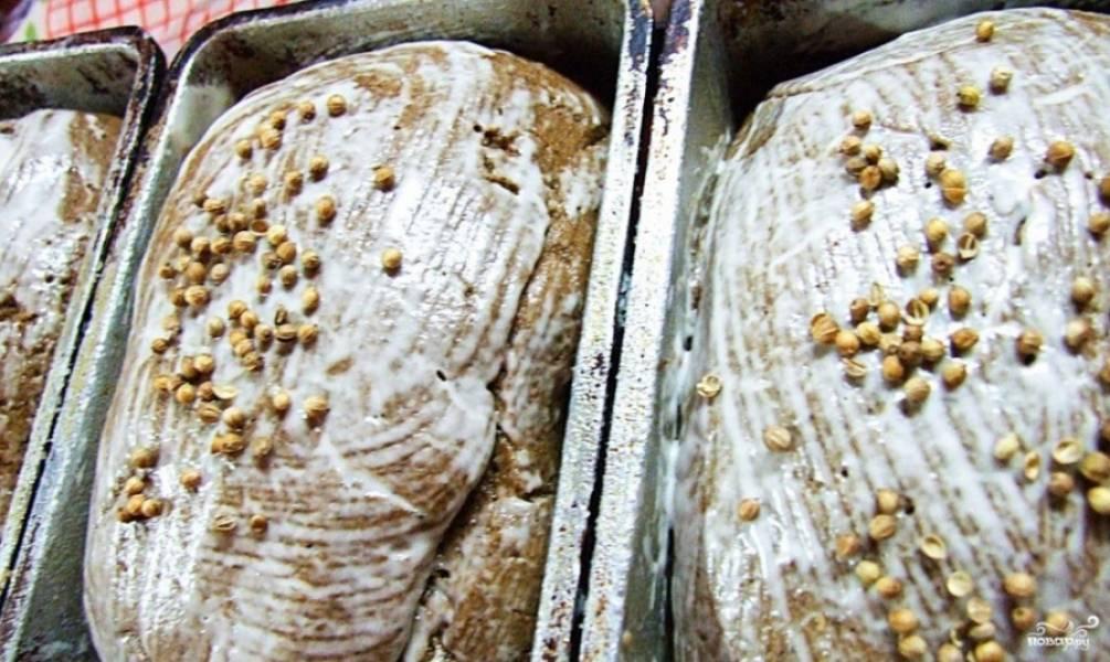 3. Теперь тесто разминаем, делаем хлебные батоны, выкладываем их в формы. Пусть еще на расстойке 40 минут постоят. Сделаем болтушку: разведем крахмал в 2 ст.л. воды, смажем этой смесью батоны сверху, посыпаем кориандром.
