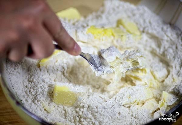 3. Вилкой или острым ножом превратите тесто в однородную крошку. Работать нужно быстро, чтобы масло не таяло.
