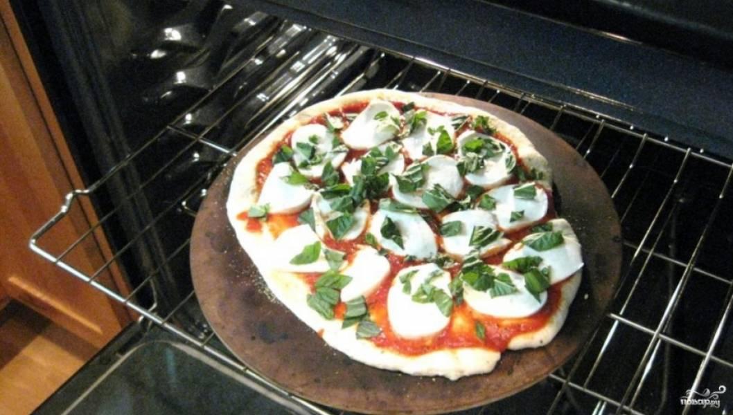 2. Посыпаем пиццу измельченным базиликом и отправляем в разогретую до 180 градусов духовку на полчаса.
