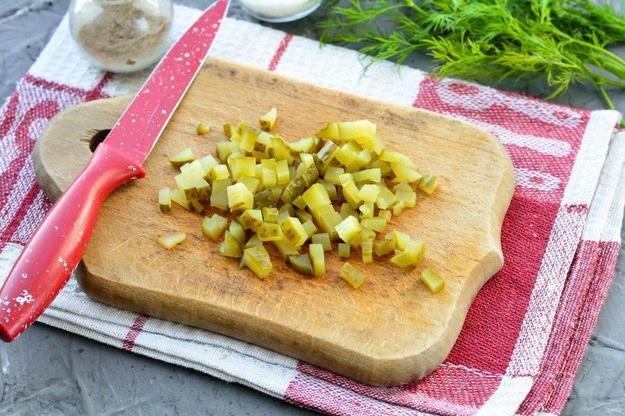 Нарежьте кубиками соленые огурцы.