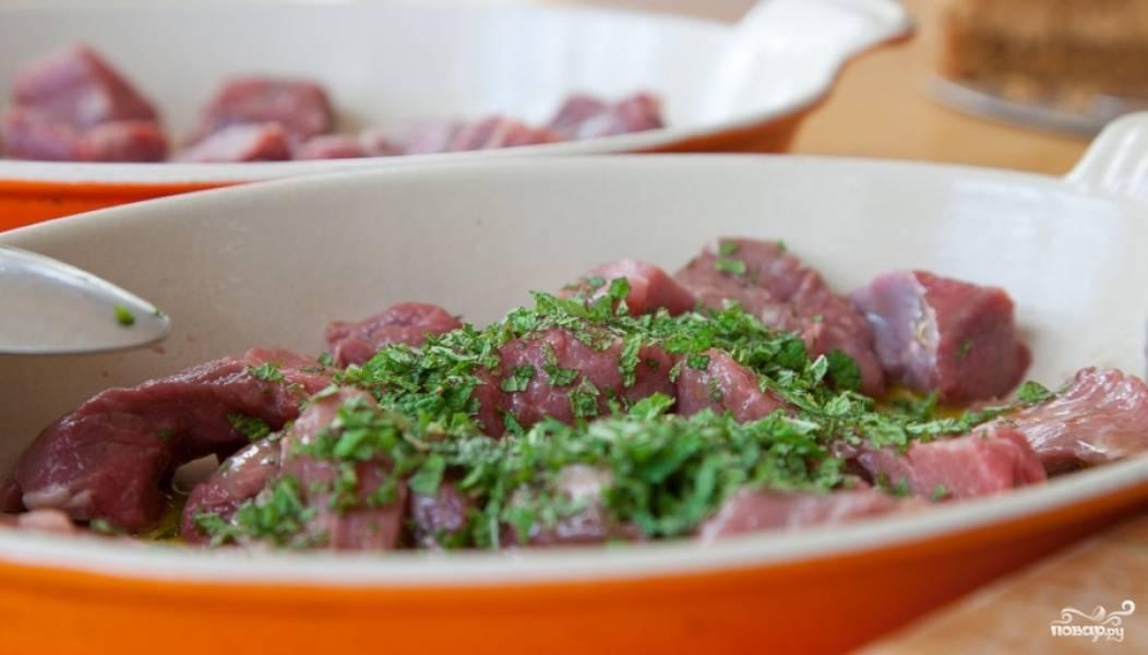 Нарезаем баранину на небольшие кусочки, обрезаем нежелательную жировую прослойку. Разделяем нарезанное мясо на две миски, где одну часть смешиваем с нарезанной мятой и оливковым маслом.