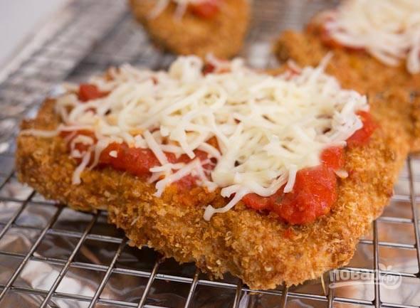 """7. Достаньте грудки из духовки, смажьте сверху томатной пастой и посыпьте натерым сыром """"Моцарелла"""". Допекайте сочное мясо в духовке до готовности при температуре 70 градусов до расплавления сыра."""