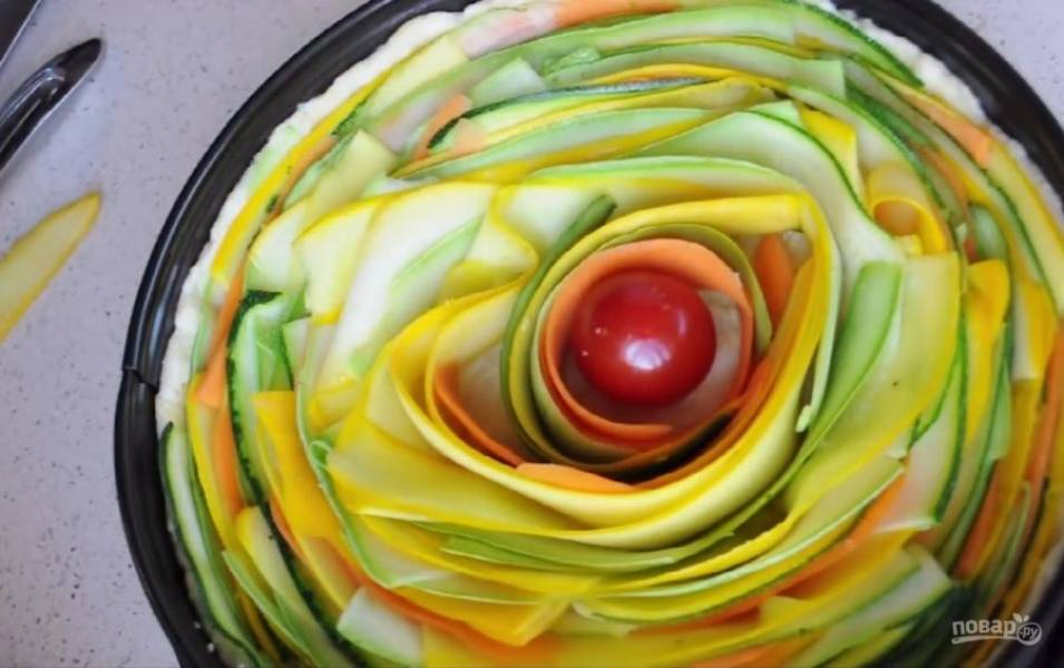 3. Тем временем нарежьте с помощью овощечистки овощи на тонкие полоски. Достаньте тесто из холодильника, выложите нарезанные овощи по краям, двигаясь к центру. В центр положите помидор черри для украшения.