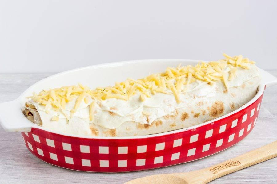 Смажьте соусом и посыпьте сыром. Поставьте в разогретую до 180 градусов духовку на 20-25 минут.