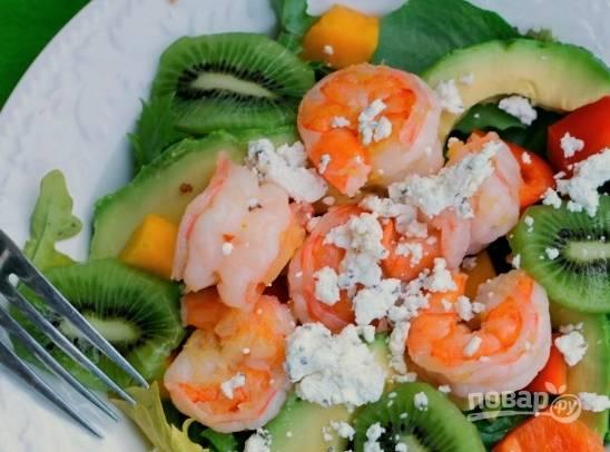 4. А теперь красиво раскладываем салатные листья по салатнице, наверх выкладываем овощи, фрукты и креветки, перемешаем, добавим специи и масло, и посыплем сверху сыром. Готово!