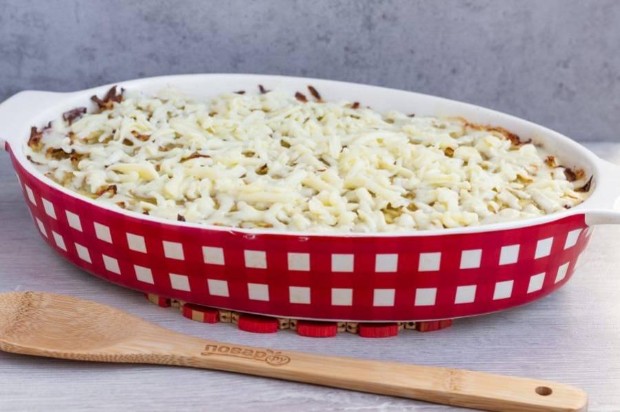 """Сыр натрите на крупной терке. По истечении времени достаньте запеканку, посыпьте сыром и поставьте ещё на 10 минут в духовку. Если есть режим """"гриль"""", то в конце три минуты можно запечь сыр под грилем при температуре 220 градусов."""