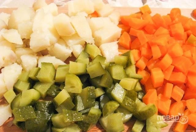 2.Очистите картошку, морковь и остудите. Нарежьте их небольшими кусочками. Такими же кусочками нарежьте маринованные огурцы и отварные яйца.
