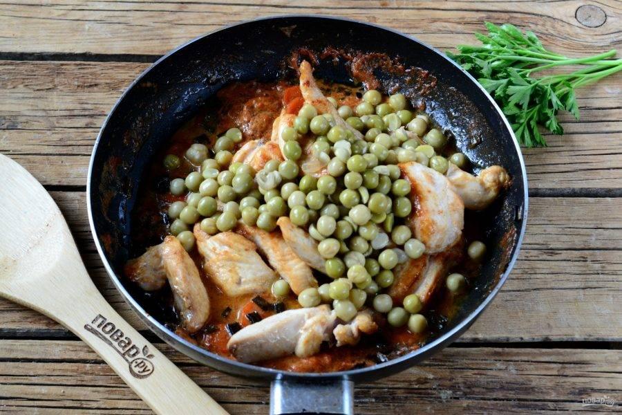 Следом положите в сковороду консервированный горошек. Перемешайте и готовьте несколько минут.