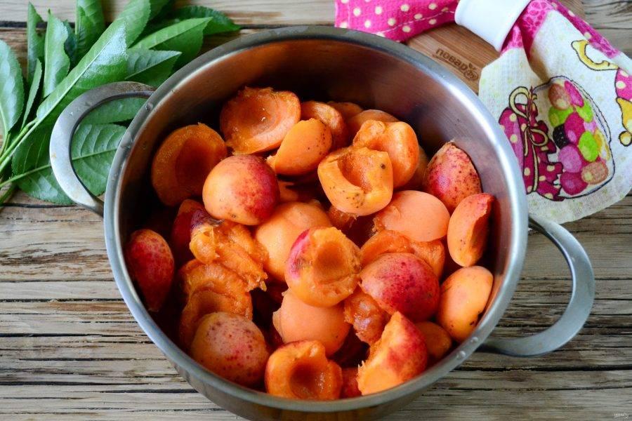 Абрикосы переберите, удалите все поврежденные плоды. Ополосните фрукты, удалите косточки. Половинки абрикосов поместите в кастрюлю с толстым дном.