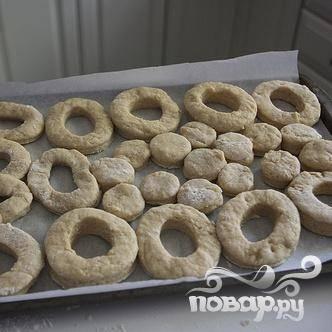 4. Выложить пончики на противень, выстеленный пергаментом, и поставить в холодильник. Налить достаточное количество растительного масла в глубокую сковороду, слоем 2,5-3,5 см. Разогреть масло на сильном огне, до тех пор, пока температура не достигнет 185-188 градусов. Пока масло греется, приготовить глазурь.