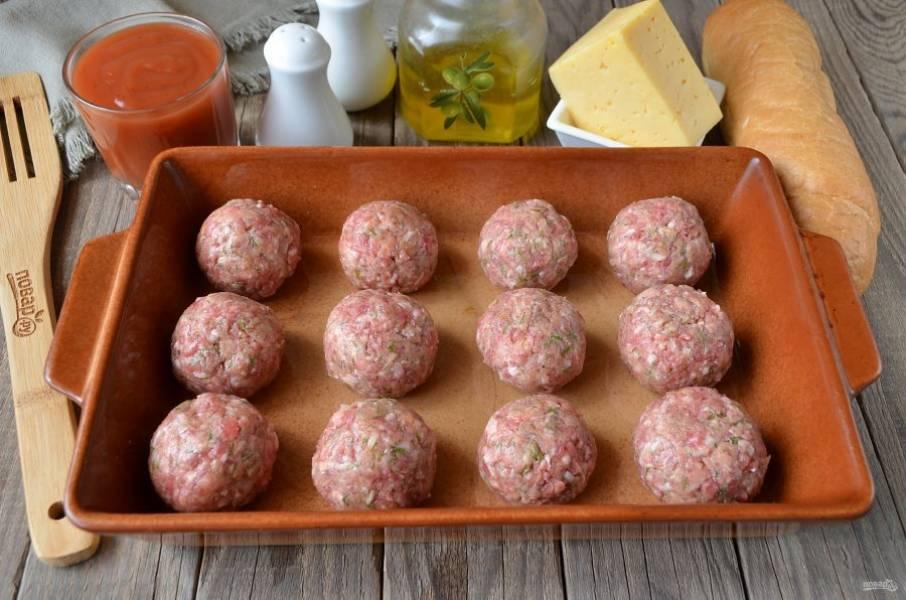 Влажными руками скатайте 12 шариков. Поместите их на смазанный противень или в огнеупорную форму. Отправьте в духовку на 20 минут, температура — 200 градусов.