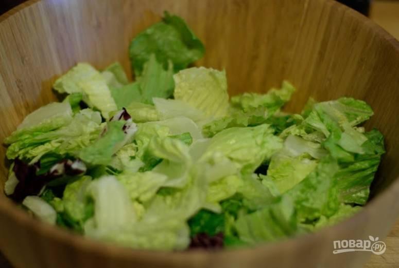 Листья салата тщательно промываем, рвем руками и кладем в салатницу.