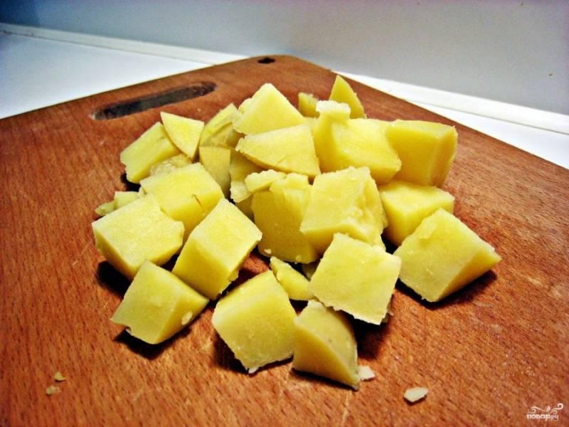 Отварите картошку в мундирах. Почистите, порежьте крупными кубиками.