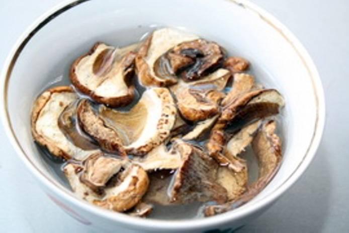 Сухие грибы промойте и замочите в горячей воде на 2 часа. Затем отварите их в кипящей воде полчаса. Слейте грибной отвар в отдельную посуду, а грибы выложите остывать. Картофель порежьте на куски и поставьте вариться в подсоленной воде.
