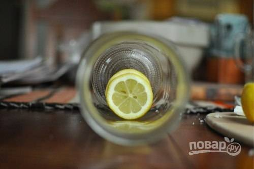 2. Очистите и измельчите чеснок. Лимон вымойте и нарежьте тонкими ломтиками. На дно баночки выложите пару ломтиков лимона, несколько кусочков чеснока и горошинок перца.