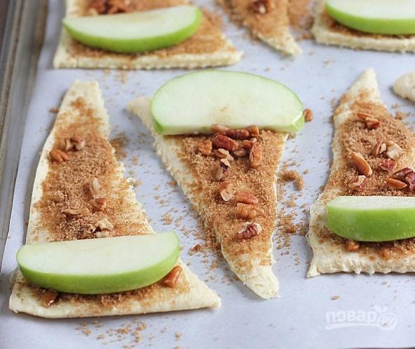 3.Вымойте яблоко, разрежьте пополам и удалите семена, нарежьте тонкими ломтиками. Выложите по одному кусочку на широкий край.