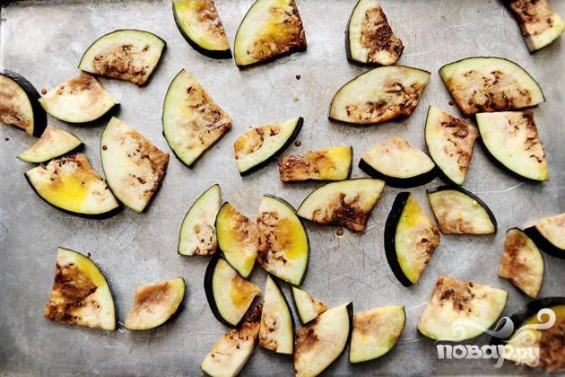 Разложить баклажаны на большом листе для выпечки. Полить оливковым маслом и поперчить. Запекать около 3 минут.