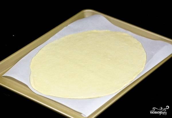 8. Подошедшее тесто разделите на две части. Раскатайте тонко и выложите на лист пергамента.