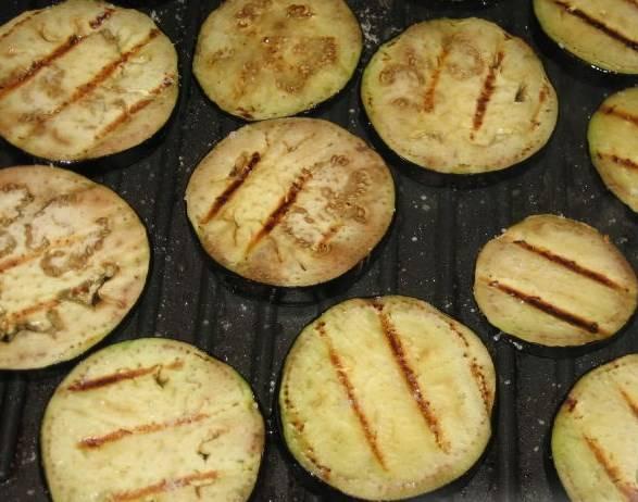 Обжарить баклажаны до готовности на гриле или на сковороде-гриль. Сковороду смазываем маслом. Баклажаны солим в процессе жарки.