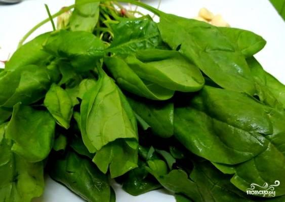 Через 15 минут режем шпинат, кладем его в суп. Его нужно варить не больше пяти минут, иначе витамины сгорят в кипятке. Докладываем остальной лук, можно добавить чеснок и зеленый лучок.