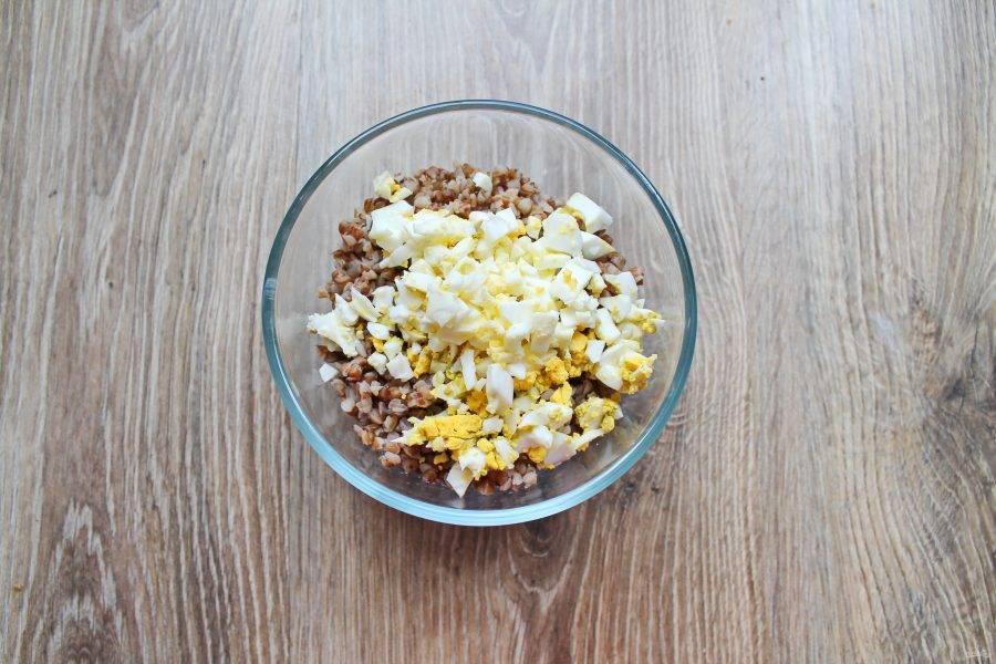 Яйца почистите и мелко порежьте. Добавьте их в отварную гречку и перемешайте.