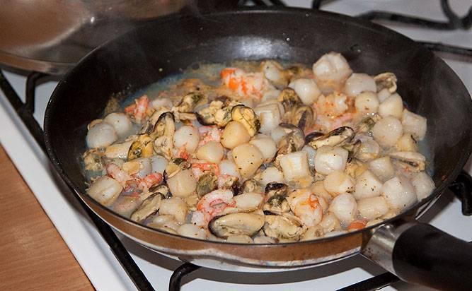 Лук и морковь отправляем в суп. Также закладываем порезанный картофель. Тем временем, обжарьте на сковороде морепродукты, добавив приправы по вкусу. Обжаренные морепродукты закладываем в бульон.