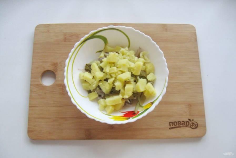 Картофель сварите, охладите и нарежьте кубиками. Выложите в салат.
