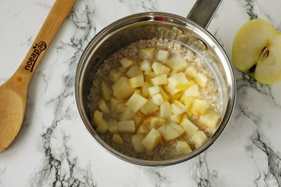 После закипания добавьте нарезанное кубиками яблоко и варите хлопья согласно инструкции на упаковке (в зависимости от их вида).